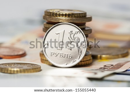 coin one ruble and the European currency: banknotes of five and fifty euro coins - stock photo