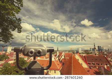 Coin Operated Binocular viewer over European city skyline landscape with blue sky and beautiful clouds  - stock photo