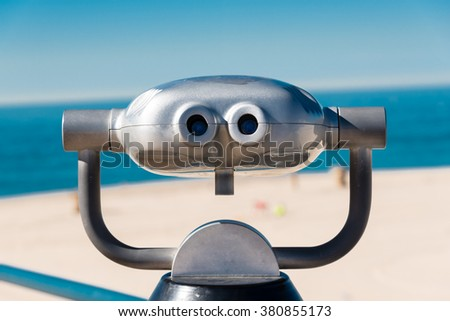 coin operated binoculars on a pier overlooking the beach