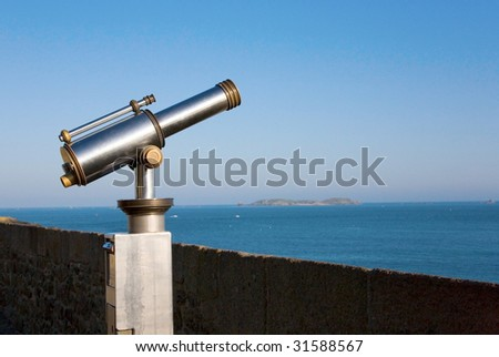 Coin operated viewfinder telescope overlooking sea shore - stock photo