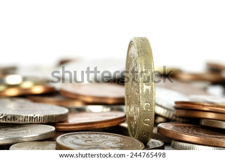 Coin set upright, towers over other coins - stock photo