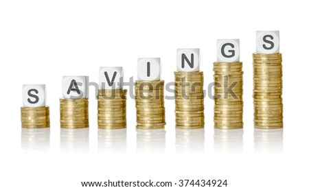 Coin stacks with letter dice - Savings - stock photo