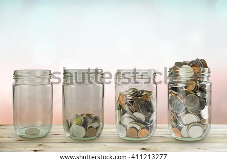 Coin stacks with the protect umbrella on wooden table over blurred background, business idea and insurance concept