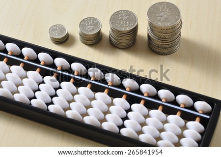 Coin With Abacus on Wooden Table, Focus on Coin - stock photo