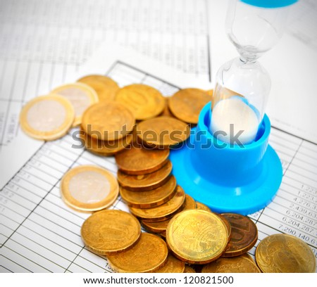 Coins and a sand-glass on documents. - stock photo