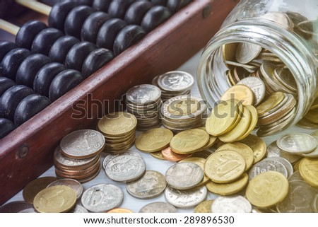 Coins and Abacus for growing business - Saving money  - stock photo
