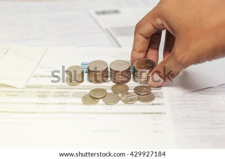 Coins and bill with hand saving for life, Money for income and expenditure saving for tax, Business diagram on financial report with coins selective focus - stock photo