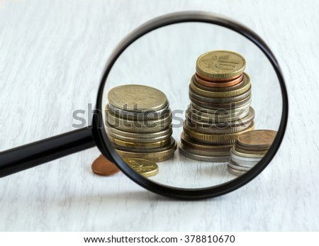 coins and magnifying glass on a light background, close-up, vintage