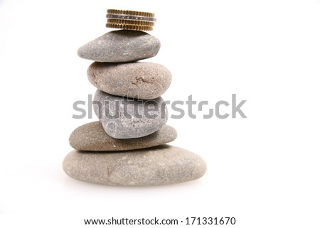 Coins and Pepples on white background as a symbol for financial balance