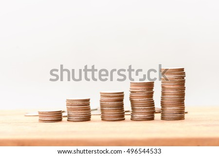 coins arranged as a graph on wood table with white background