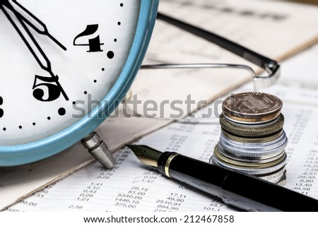 Coins, clock, spectacles and fountain pen on a data table - stock photo