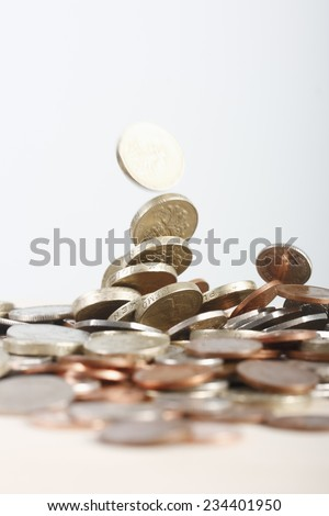 Coins falling our of the sky onto a table. - stock photo