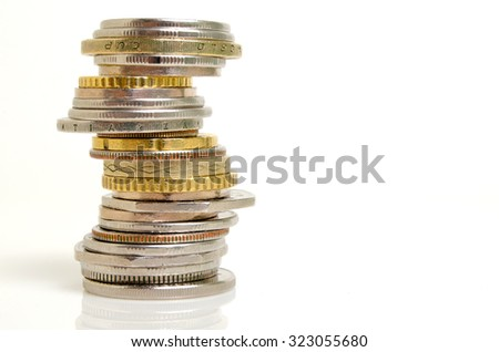 Coins from different countries stacked against a light background.