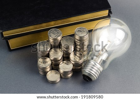 Coins heap with book and light bulb, smart investment, business idea or use in education concept - stock photo