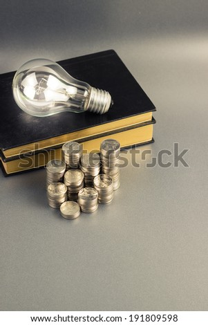 Coins heap with book and light bulb, smart investment, business idea or use in education concept