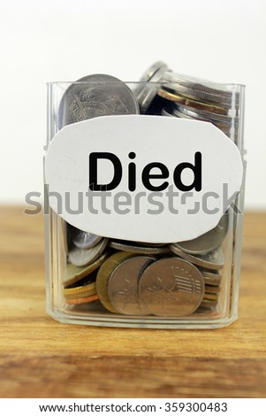 Coins in a glass container with a label died. Financial concept.