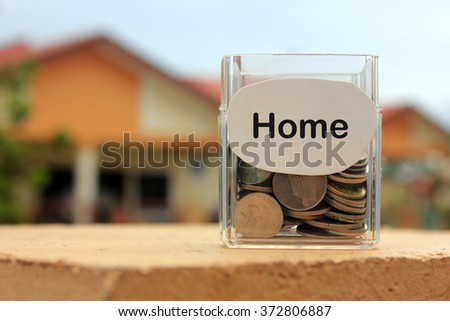 Coins in a glass container with a label home . Financial concept.
