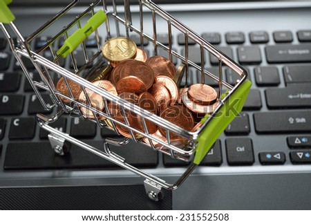 coins in a metal basket on a black keyboard - stock photo