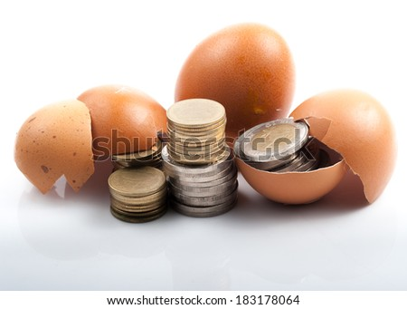 Coins in broken golden eggshell over white background.