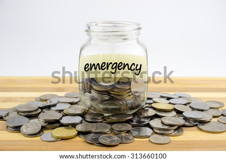 Coins in glass container with EMERGENCY label on wooden surface against white background.Financial concept.Selective focus. - stock photo