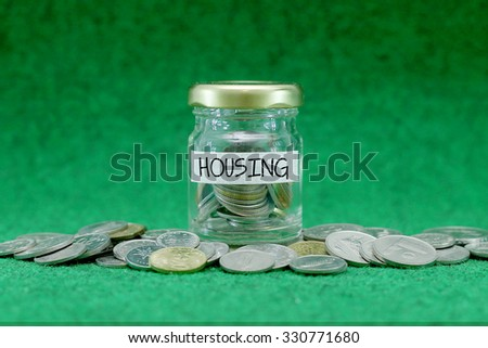Coins in glass container with HOUSING label on rusty green background.Financial concept.Selective focus. - stock photo
