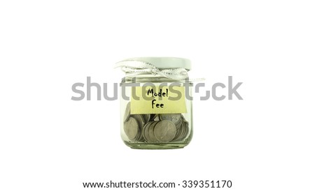 Coins in glass container with MODEL FEE label white background. Saving money concept. Selective focus and shallow Depth of Field. - stock photo