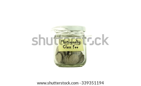Coins in glass container with PHOTOGRAPHY CLASS FEE label white background. Saving money concept. Selective focus and shallow Depth of Field. - stock photo