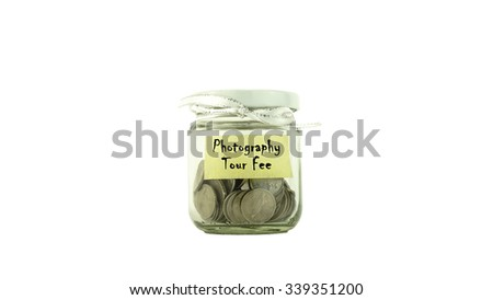 Coins in glass container with PHOTOGRAPHY TOUR FEE label white background. Saving money concept. Selective focus and shallow Depth of Field. - stock photo