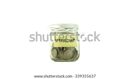 Coins in glass container with SPEEDLIGHT label white background. Saving money concept. Selective focus and shallow Depth of Field.