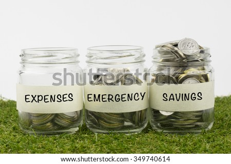 Coins in glass jar contains coins for expenses, emergency and savings. financial concept. Selective focus and shallow depth of field - stock photo