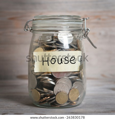 Coins in glass jar with house label, financial concept. Vintage wooden background with dramatic light. - stock photo