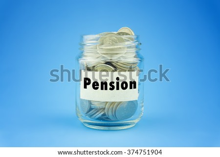 Coins in glass jar with pension label over blue background, financial concept. Selective focus and shallow depth of field