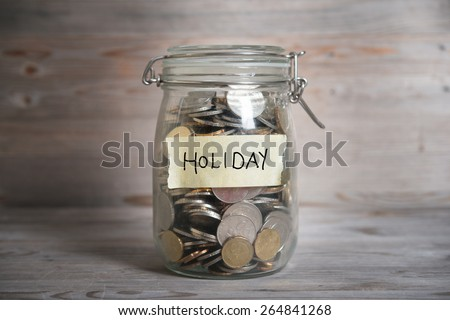 Coins in glass money jar with holiday label, financial concept. Vintage wooden background with dramatic light. - stock photo