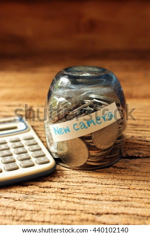 coins in glass with calculate for new camera,money save concept  - stock photo