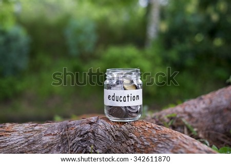 Coins in glass with EDUCATION label against bokeh background.Financial concept.Selective focus.