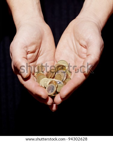 Coins in hands on black background.