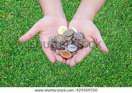 Coins in hands on grass,Donation Investment Fund Financial Support Charity  Dividend Market Growth Home House Stock Trust Wealthy Giving Planned Accounting Collection Debt Banking ROI concept - stock photo