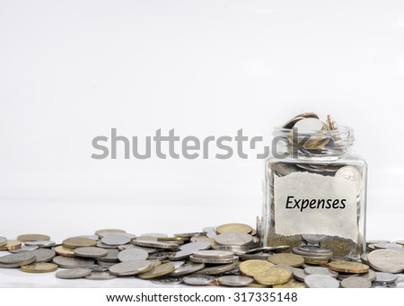 coins in jar with expenses label in isolated white background; financial concept - stock photo