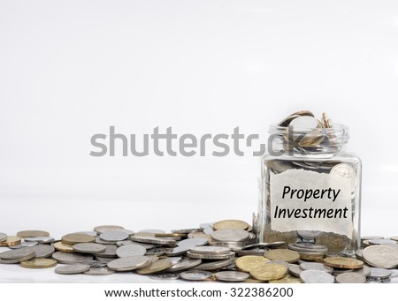 coins in jar with property investment label in isolated white background; financial concept - stock photo