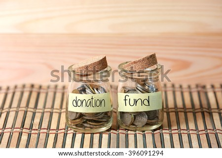 Coins in jar. Writing Donation Fund on two jar with wooden pallet background. Selective focus with shallow depth of field. - stock photo