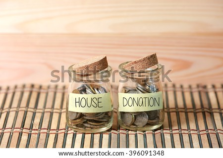 Coins in jar. Writing House Donation on two jar with wooden pallet background. Selective focus with shallow depth of field. - stock photo