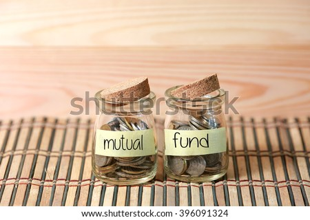 Coins in jar. Writing Mutual Fund on two jar with wooden pallet background. Selective focus with shallow depth of field. - stock photo