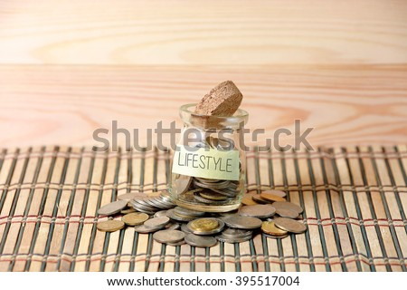 Coins in money jar,writing INSURANS with wooden pallet background. Selective focus with shallow depth of field. - stock photo