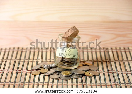 Coins in money jar,writting CHINESE NEW YEAR with wooden pallet background. Selective focus with shallow depth of field. - stock photo