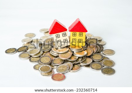 coins in pile and house isolated image - stock photo