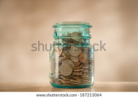 Coins in savings jar full of money - stock photo