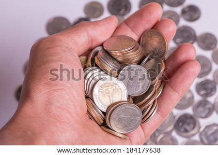 coins in the hand on pile of coins background - stock photo