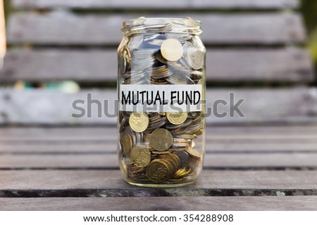 Coins in the jar or glass on the wood with MUTUAL FUND label against bokeh background. Financial concept. Selective focus. - stock photo