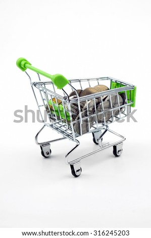 Coins in the shopping cart isolated on white background