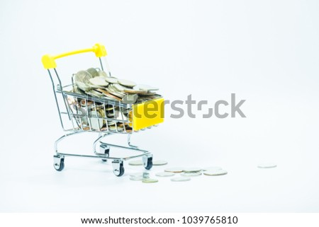 Coins in yellow shopping cart with copy space and white background. Close up shot.